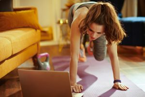 young sports woman in fitness clothes at modern home using online streaming fitness site in laptop and doing circuit training on fitness mat.